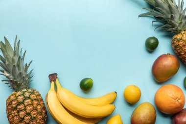 top view of ripe exotic fruits on blue background with copy space
