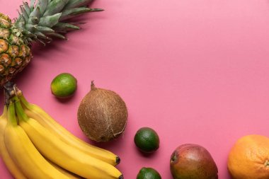 Top view of ripe tropical fruits on pink background with copy space stock vector