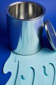 üres fém fényes lehet és csöpögő papír vágott festéket a fényes kék háttér