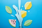 Fotografie top view of bottle with paper cut water splash, lemons, leaves and watermelon on blue background
