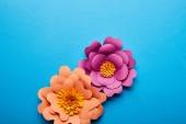 top view of colorful purple and orange paper cut flowers on blue background