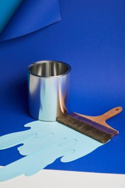 metal shiny can, brush and dripping paper cut paint on bright blue background