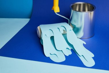 metal shiny can and roller with dripping paper cut paint on bright blue background