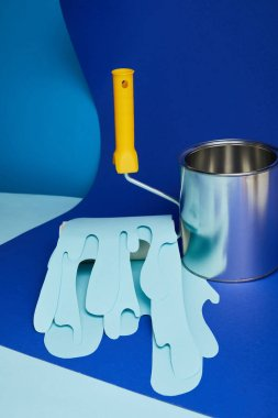 metal shiny can near roller with dripping paper cut paint on bright blue background