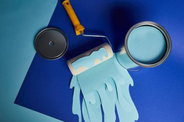 top view of metal shiny can near roller with dripping paper cut paint on bright blue background