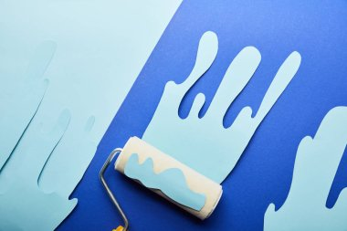 top view of roller with blue paper cut dripping paint on bright background
