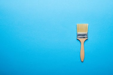 Top view of brush on bright blue background with copy space stock vector