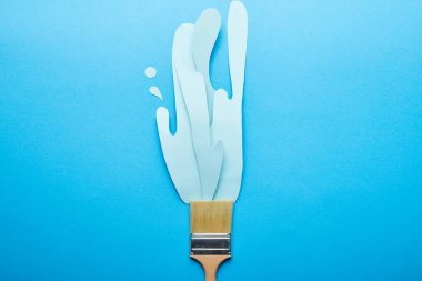 Top view of brush with dripping paper cut paint on bright blue background stock vector