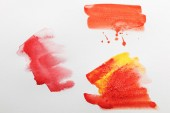 Fotografie Draufsicht auf gelb und rot gemischte helle Aquarell-Pinselstriche auf weißem Papier