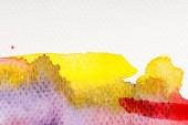 Fotografie Nahaufnahme von gelben, lila und roten Aquarellfarben auf weißem Hintergrund mit Kopierraum