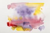 Draufsicht auf gelbe, lila und rote Aquarelle, die nasse Farbe auf weißem Papierhintergrund verschüttet