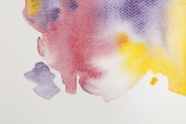 close up view of yellow, purple and red watercolor paint spills on white background