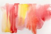 Fotografie Draufsicht auf gelb und rot feuchte Aquarellfarbe verschüttet auf strukturiertem Papier Hintergrund
