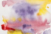 Draufsicht auf gelbe, lila und rote Aquarellfarbe auf strukturiertem Hintergrund