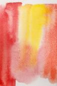Fotografie Nahaufnahme von blassgelben und roten Aquarell-Pinselstrichen auf strukturiertem Hintergrund