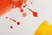 Nahaufnahme von gelben und roten Aquarell-Pinselstrichen mit Tropfen auf weißem strukturiertem Hintergrund