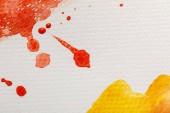 Nahaufnahme der gelben und roten Aquarellfarbe verschüttet mit Tropfen auf weißem strukturierten Hintergrund