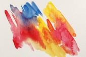 Draufsicht auf leuchtend gelbe, blaue und rote Aquarell-Pinselstriche auf weißem Hintergrund