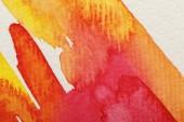 Nahaufnahme von gelben und roten Aquarell-Pinselstrichen auf strukturiertem Hintergrund