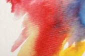 Nahansicht der bunten Aquarellfarbe verschüttet auf weißem Hintergrund