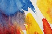 Nahaufnahme von gelben, blauen und roten Aquarell-Pinselstrichen auf weißem Hintergrund