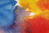 Nahaufnahme von gemischten gelben, blauen und roten Aquarellfarben auf strukturiertem Hintergrund