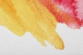 Fotografie Nahaufnahme der gelben und roten gemischten Aquarellfarbe verschüttet auf weißem Hintergrund