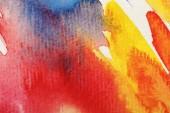 Fotografie Nahaufnahme von nassen gelben, blauen und roten Aquarell-Pinselstrichen auf weißem Hintergrund