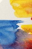 Fotografia vista ravvicinata di pennellate di vernice ad acquerello gialle, blu e rosse su sfondo bianco