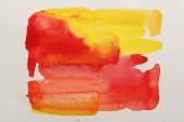 Draufsicht auf gelbe und rote Aquarellfarbe auf weißem Papier
