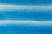 close up view of blue watercolor paint on textured paper