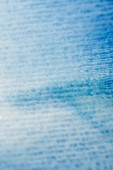 close up view of blue watercolor paint on textured paper background