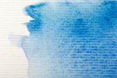 close up view of blue watercolor paint spill on white textured paper background