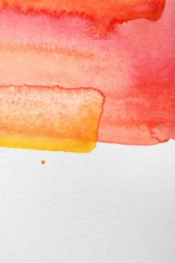 close up view of yellow and red watercolor paint spills on white background with copy space