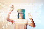 young woman in virtual reality headset pointing with hands at glowing data illustration on beige and blue background