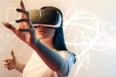junge Frau im Virtual-Reality-Headset gestikuliert zwischen leuchtenden Cyber-Illustrationen auf beigem und blauem Hintergrund