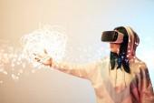 mladá žena ve virtuální realitě sluchátka ukazuje s rukou na zářící kybernetické ilustrace na béžové a modré pozadí