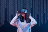 Fotografie young woman in virtual reality headset among cyber illustration on dark blue background