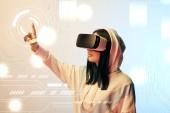 Fotografie mladá žena ve virtuální realitě sluchátka ukazuje prstem na zářící kybernetické ilustrace na béžové a modré pozadí