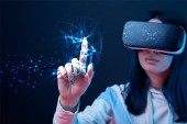 selective focus of young woman in virtual reality headset pointing with finger at glowing cyber illustration on dark background
