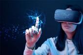 selektivní zaměření mladé ženy ve virtuální realitě headset ukazující prstem na zářící kybernetickou ilustraci na tmavém pozadí