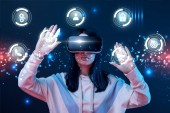 young woman in virtual reality headset gesturing among glowing cyber icons on dark background