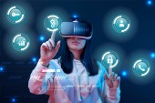 young woman in virtual reality headset pointing with fingers at glowing cyber icons on dark background