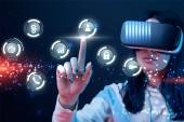 Selektiver Fokus einer jungen Frau im Virtual-Reality-Headset, die mit dem Finger auf glühende Cyber-Ikonen auf dunklem Hintergrund zeigt
