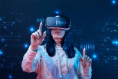 young woman in virtual reality headset pointing with fingers at glowing cyber illustration on dark background