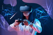 KYIV, UKRAINE - APRIL 5, 2019: Young woman in virtual reality headset using joystick on dark background with abstract illustration