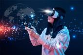 Kyjev, Ukrajina-5. dubna 2019: mladá žena s mikrofonem ve virtuální realitě používající pákový ovladač na tmavém pozadí s obrázkem zeměkoule