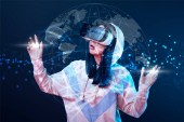 Fényképek shocked young woman in vr headset gesturing near glowing globe illustration on dark background