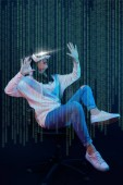 Fotografie young shocked woman in virtual reality headset sitting on chair and gesturing among data illustration on dark background