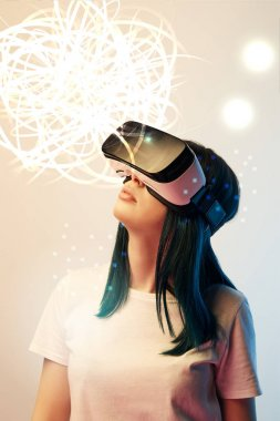 young woman in virtual reality headset looking at glowing abstract illustration on beige background